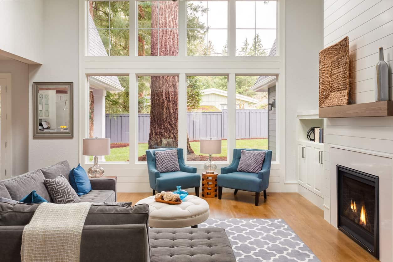 A cozy, small living room with warm hardwood floors and cool toned furniture makes for a gorgeous sight.