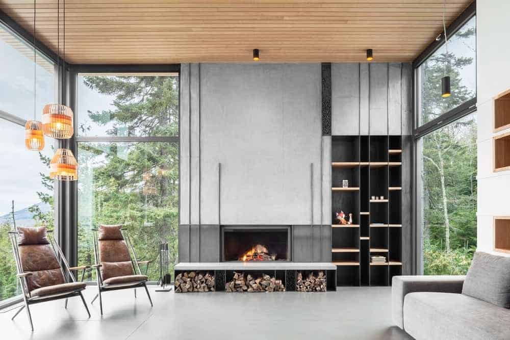 A modern living room covered with wood panel ceiling. It is surrounded with glass walls and a gray concrete wall with built-in shelves and a wood-burning fireplace. It features three orange caged pendant lights hung over two leather lounge chairs and a gray sofa on a tiled floor.