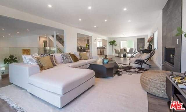 A sleek living room features a white L-shaped sectional sofa and a modern black geometric center table over a white huge rug. It also has a gray accent wall where a digital screen is mounted and is lighted by scattered recessed ceiling.