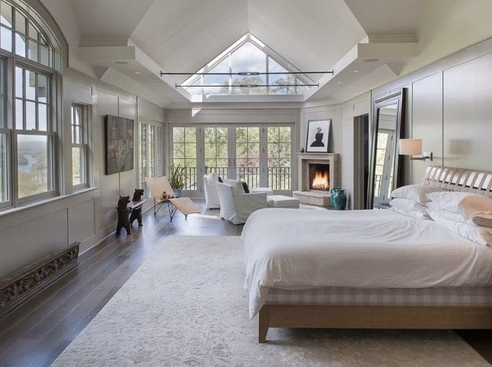 Luxury white primary bedroom with pitched ceiling, French doors, large windows, and a fireplace.