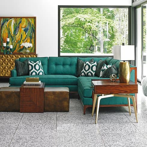 Green luxury sofa with matching throw pillows in a stylish modern living room.