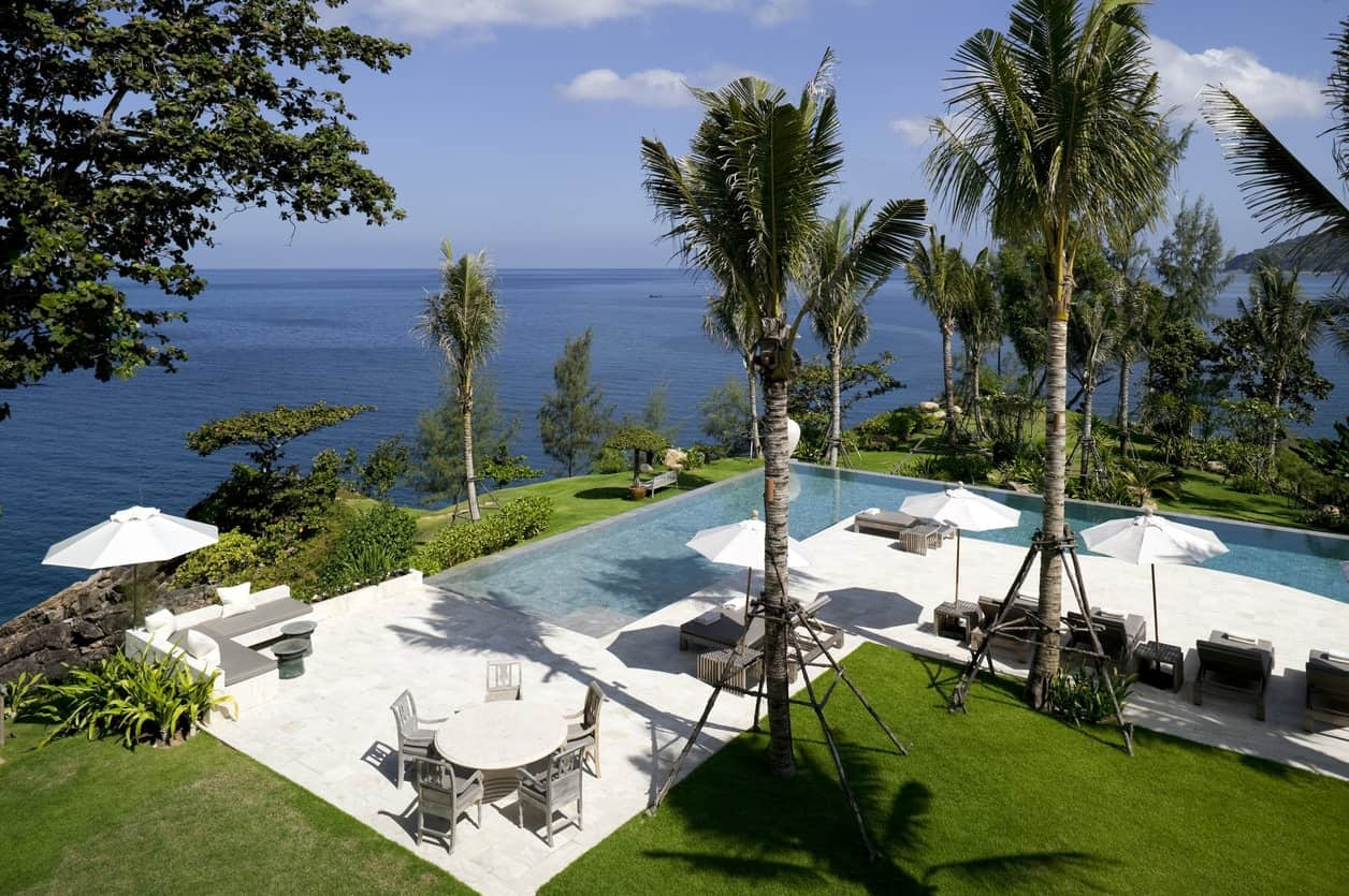 Luxury L-shaped swimming pool with palm trees and patio furniture.