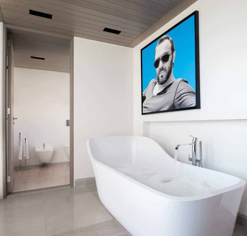 A large portrait adds a nice accent in this modern primary bathroom featuring a freestanding tub over tiled flooring that's paired with chrome fixtures. A wooden door on the side opens to the toilet area of this room.