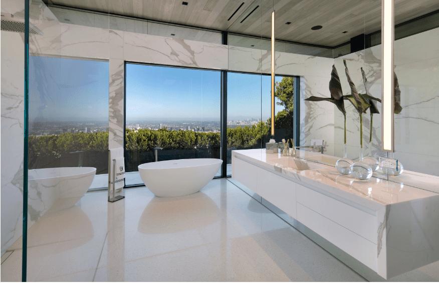 Huge modern master bathroom with long floating vanity, freestanding modern white tub and incredible views.