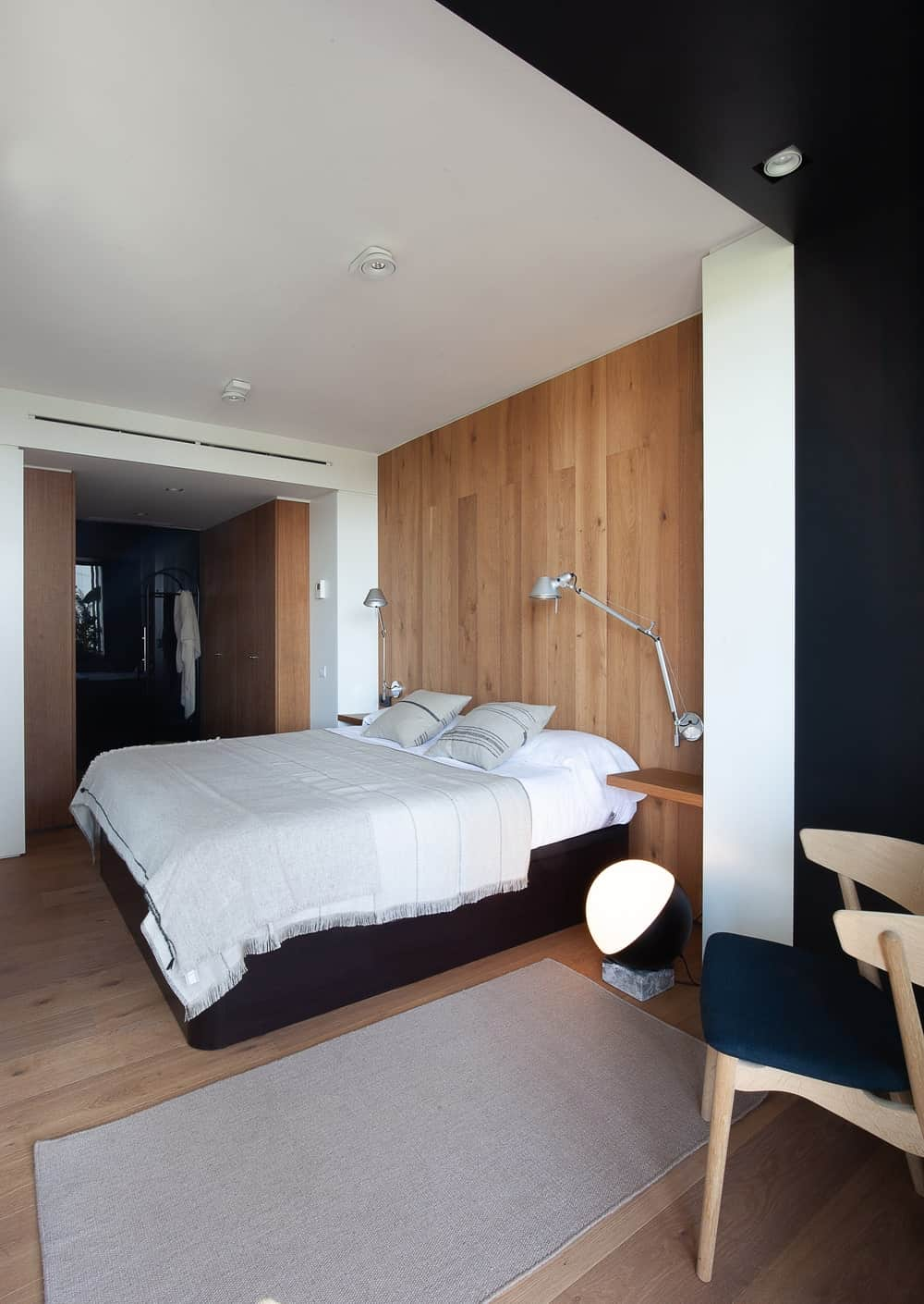 The black platform bed has contrasting white sheets. Behind it is a wooden wall that matches with the hardwood flooring that is adorned with a modern floor lamp and a gray area rug by the sitting area that has a wooden chair.