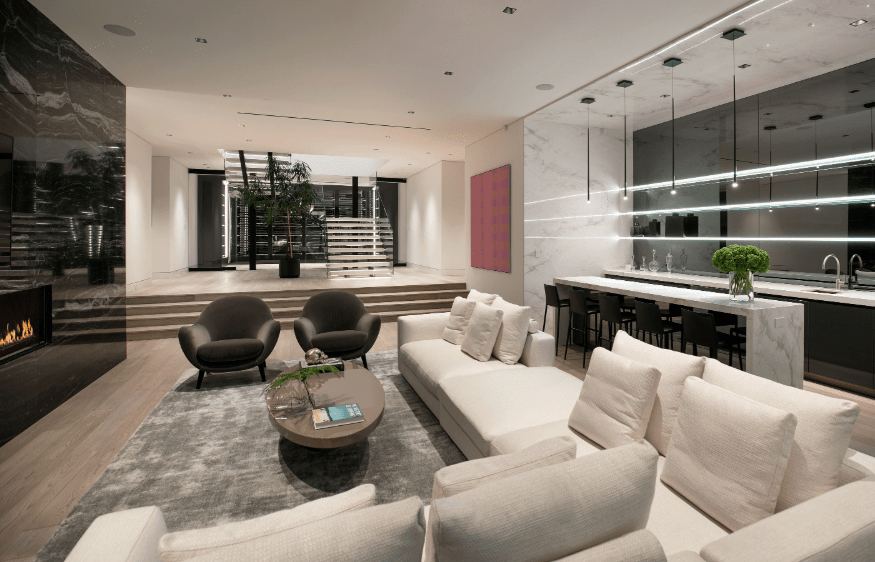 I love this sunken modern living room with huge custom white sectional sofa flanked by two black modern armchairs all facing a black accent wall with gas fireplace