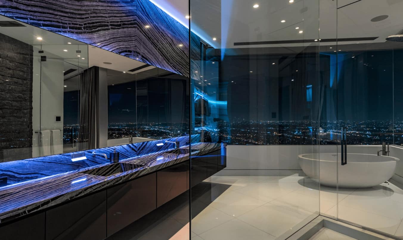 This modern primary bathroom has an amazing skyline overlooking view of the city below. This serves as a nice background for those who are relaxing on the white freestanding bathtub at the corner by the glass walls. Adjacent to this is a black floating two-sink vanity with black marble countertops.