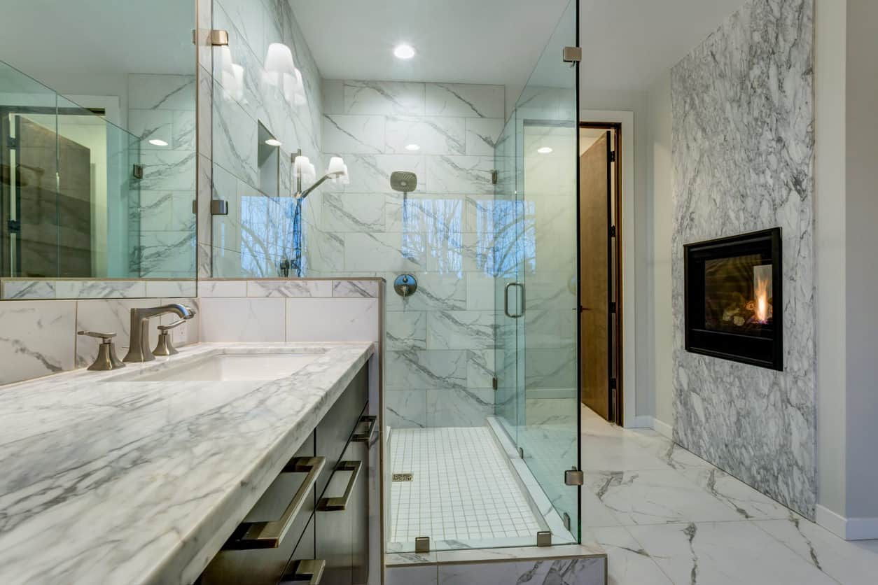 This beautiful marbled bathroom adds luxury with a mounted fireplace right in the bathroom itself! That's not something that you often see in a bathroom, but it works great in this setting.