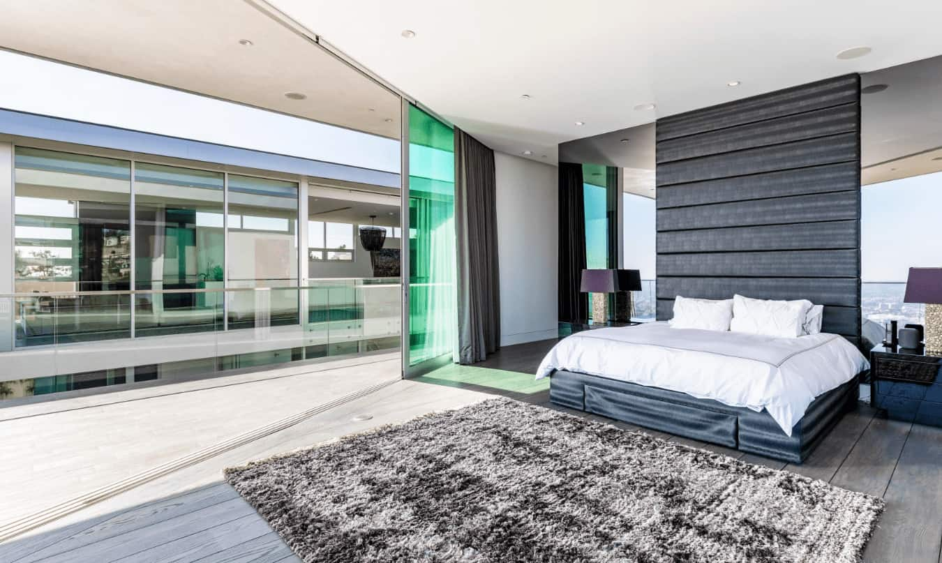 This modern bedroom boasts of a large black leather bed with a large black headboard. This bed oozes machismo that is augmented by the two large mirror panels that flank the black headboard. This pairs well with the wide hardwood flooring topped with a gray area rug.