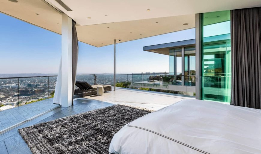 This modern bedroom has an amazing city skyline view by the foot of the bed. This amazing view can also be enjoyed on the wooden dark brown lawn chair by the edge near the glass wall that maximizes the view.