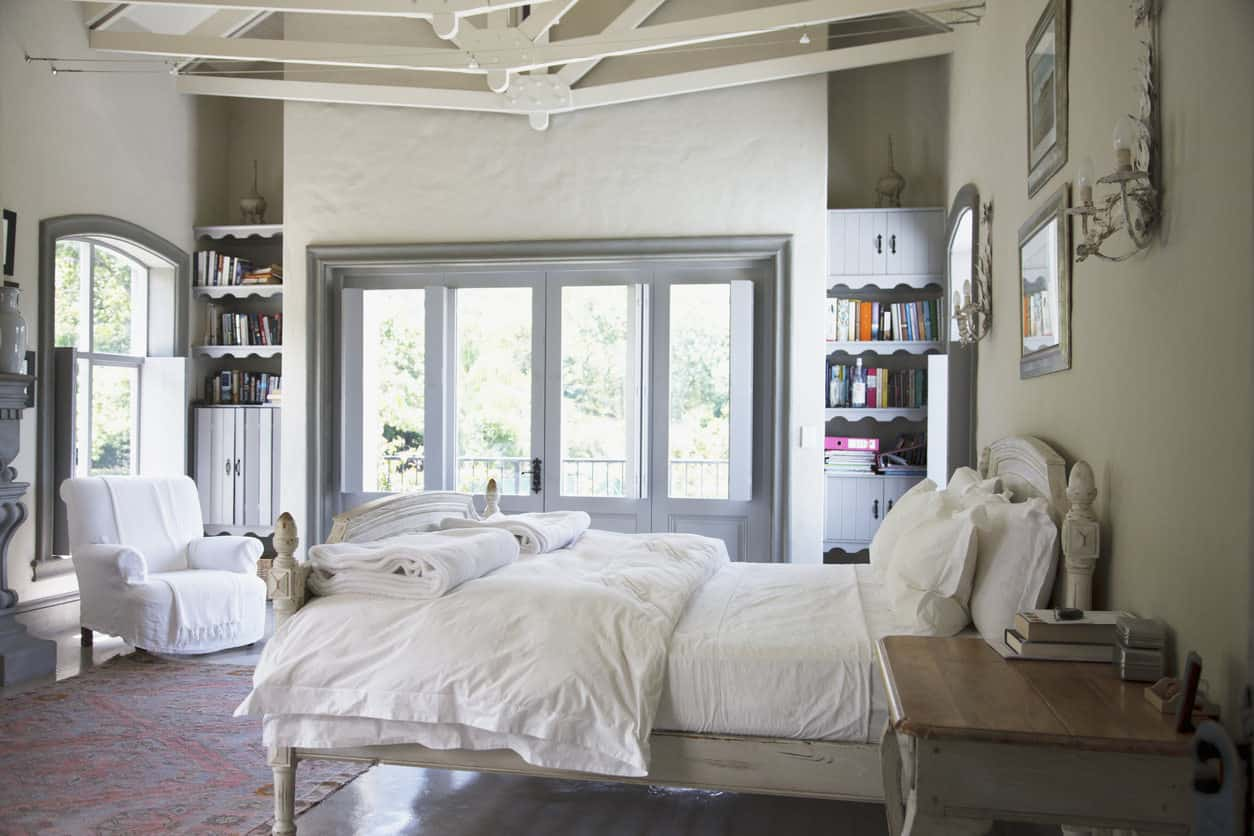 Whimsical contemporary primary bedroom with cathedral ceiling and bookshelves. The bed is a refinished ditressed wooden bed with matching nightstand table.