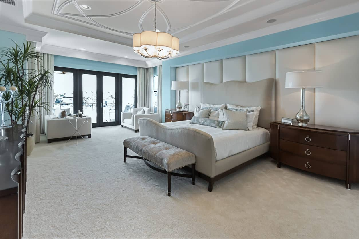 Fabulous contemporary primary bedroom that is huge and includes large sitting area, extensive crown molding, upholstered accent wall all in a light beige and light blue color scheme.