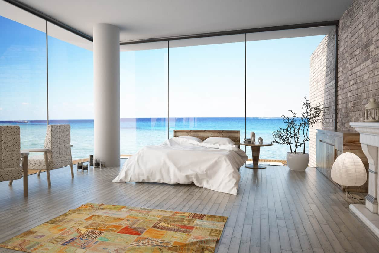 I just love this primary bedroom with floor-to-ceiling windows overlooking the ocean. One wall is all brick which really works well with the glass and wood flooring. The brick wall includes a fireplace. This is one cool bedroom.