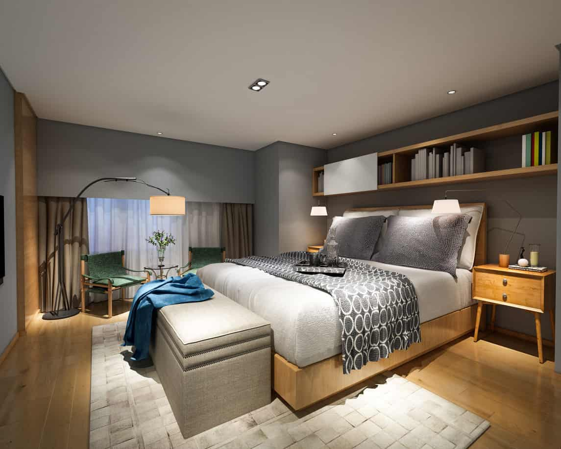 Contemporary primary bedroom with large storage bench, wood flooring, gray walls and a small sitting area. This is a great example of a nice design that didn't require a lot of money.