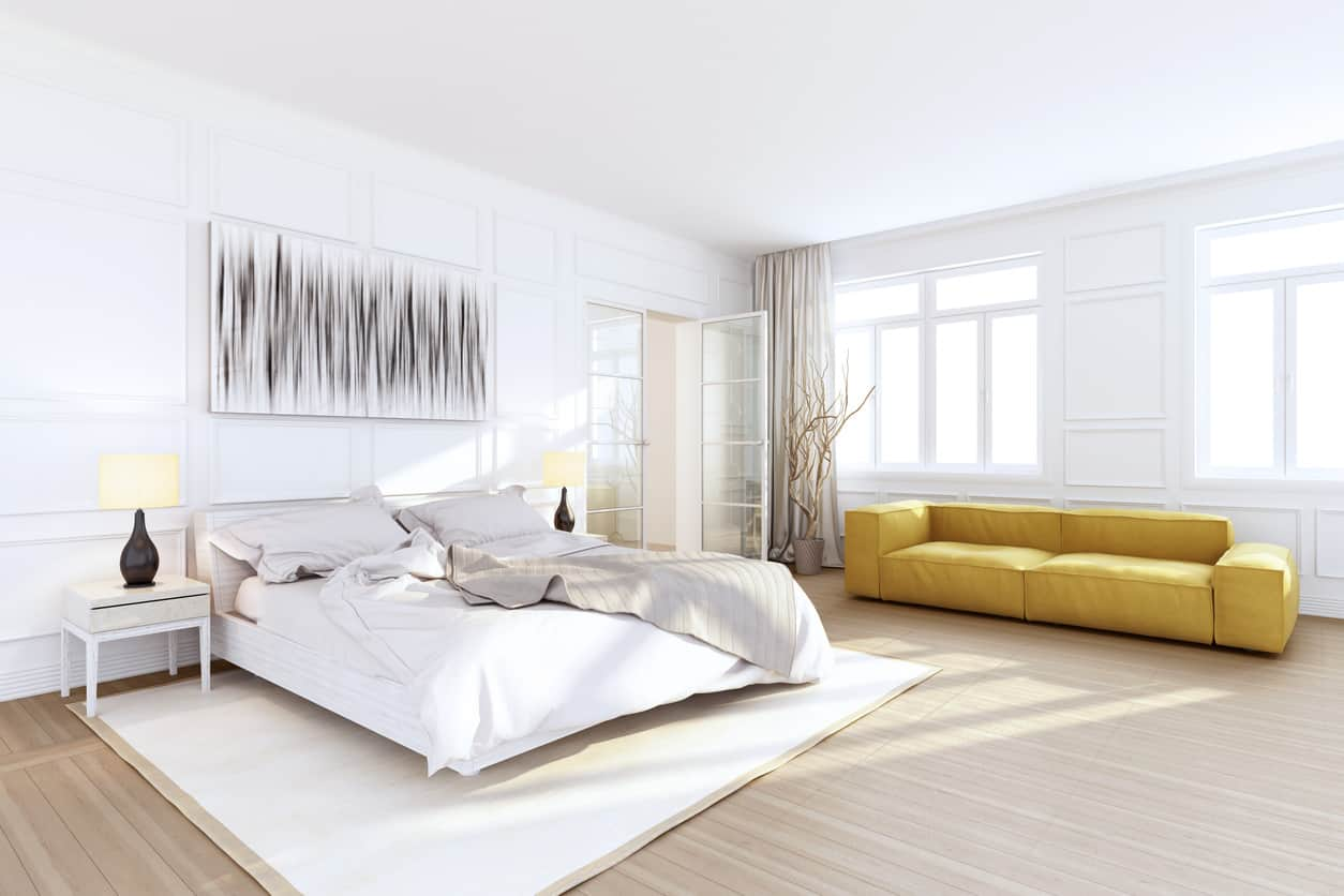 Spacious white primary bedroom with sofa, large white area rug, light wood floor and white ceiling and walls. I love the white wood paneling on the walls - that really makes a difference.