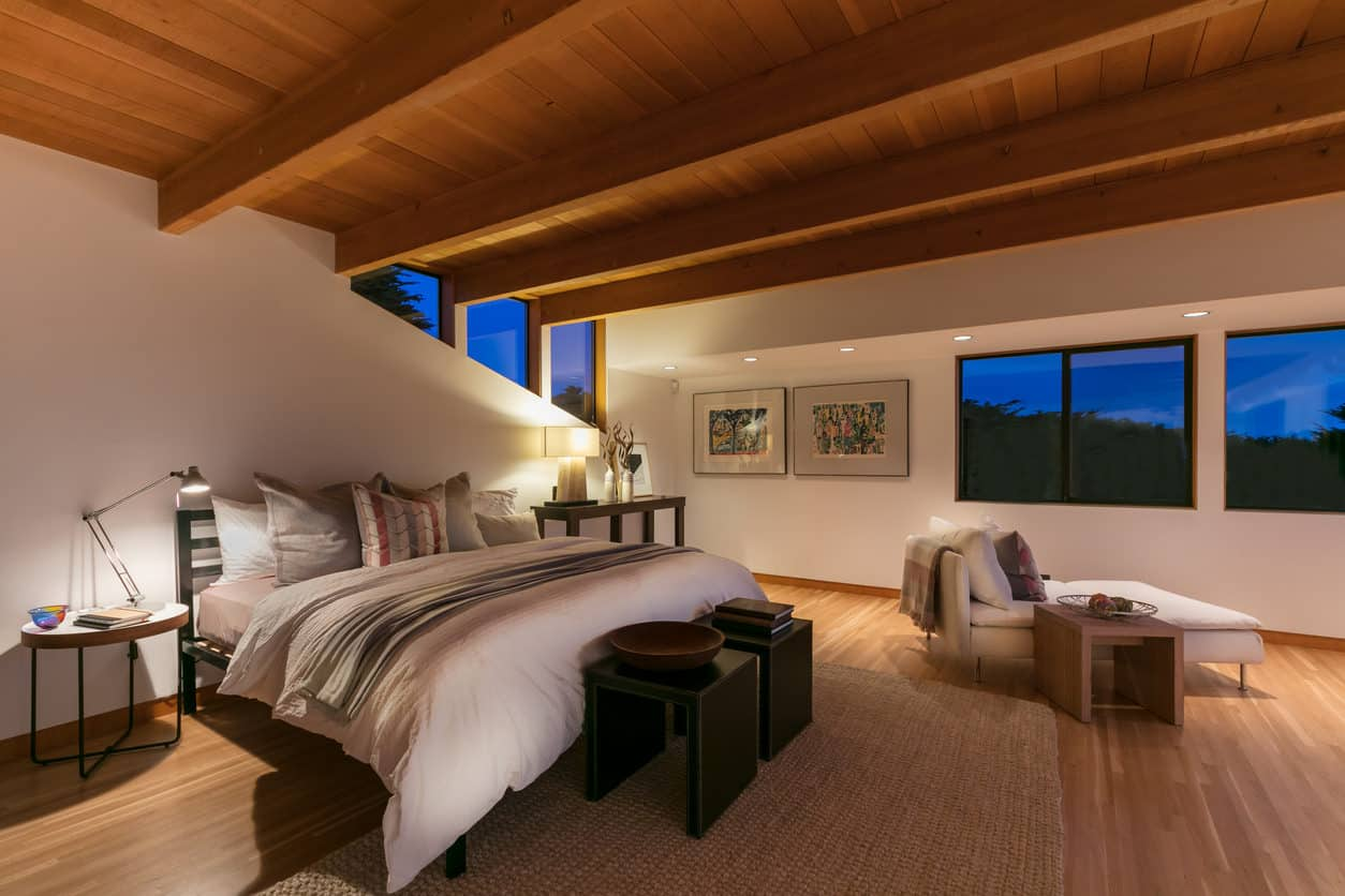 A gorgeous contemporary large primary bedroom with wood-beamed ceiling, white walls, wood floor and angled windows.