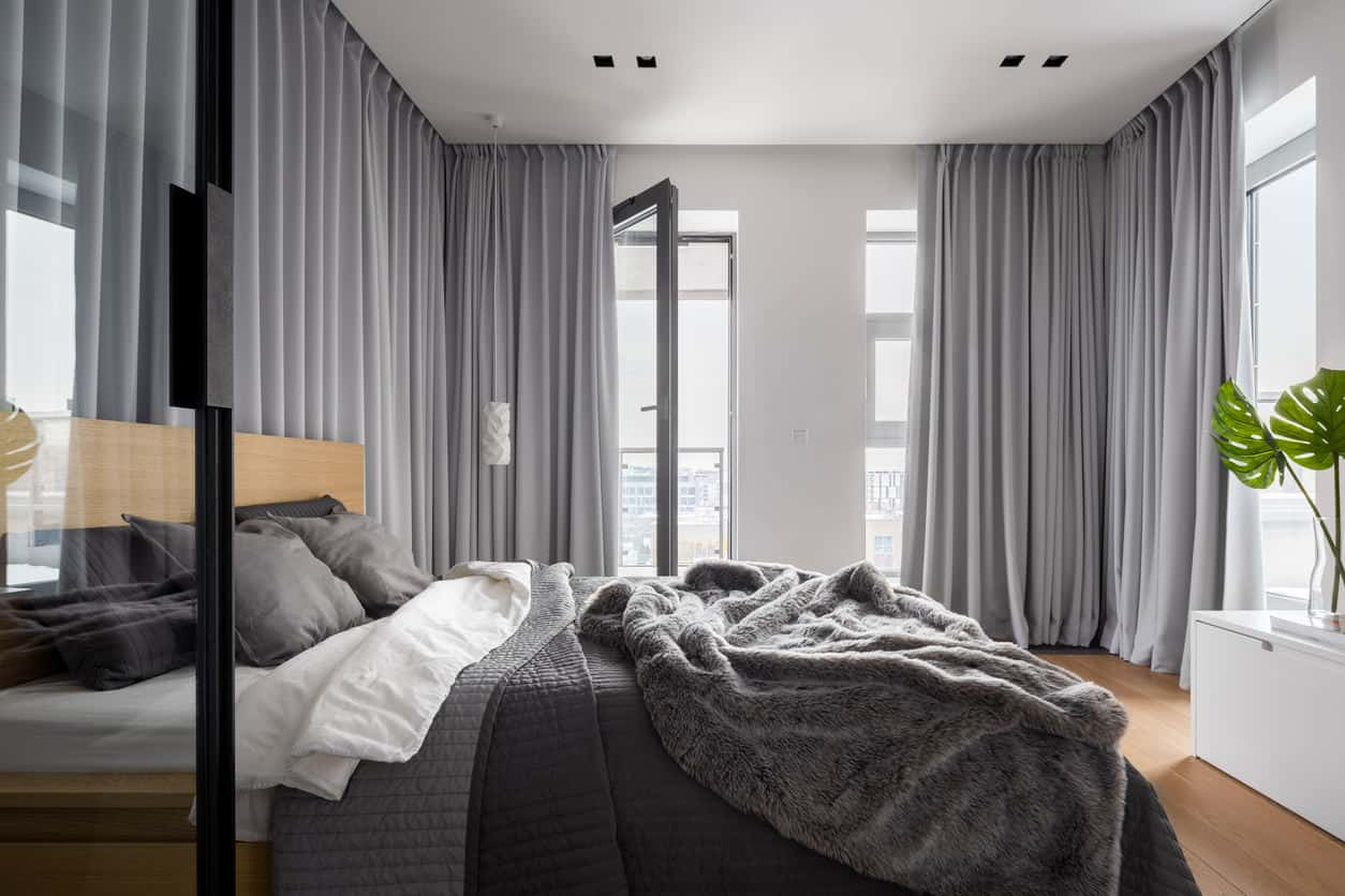 Simple contemporary primary bedroom with floor-to-ceiling gray drapes providing extensive privacy.