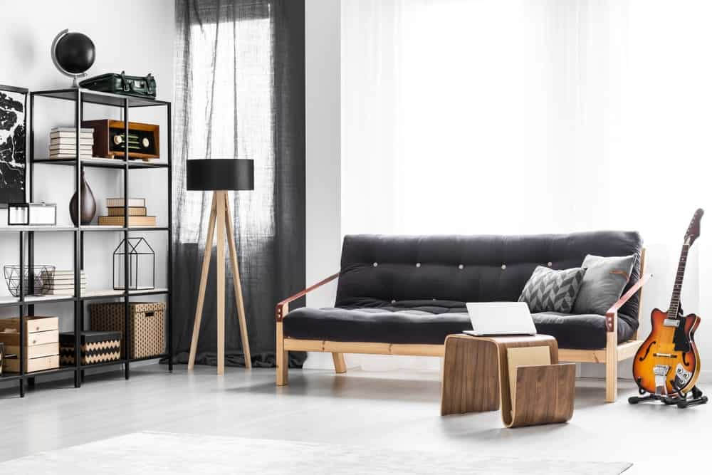 White music room furnished with black and wooden furniture pieces.
