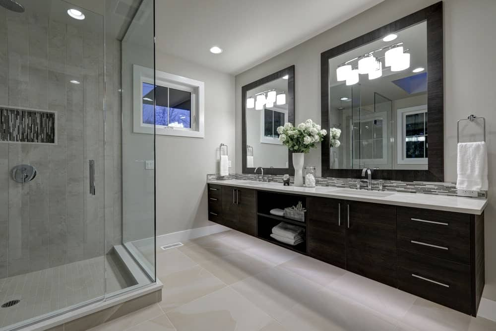 Modern primary bathroom with glass-enclosed shower, floating vanity and double sink.