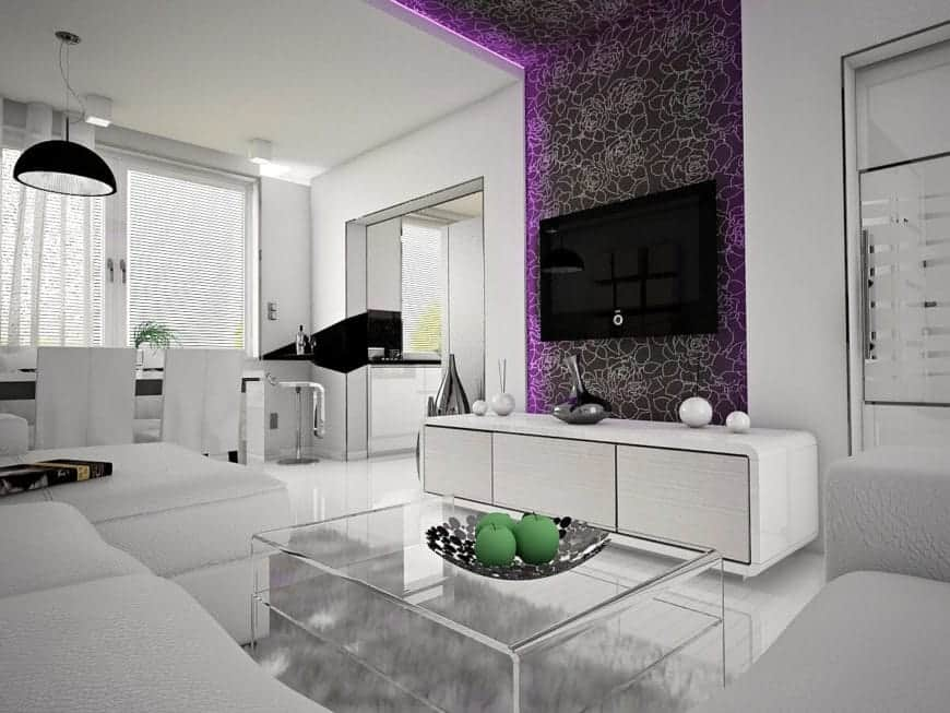 A clean all-white living room highlighted with a floral wallpaper that's lined with purple LED lights. It has a huge white sofa wrapped around a glass coffee table over a gray shaggy rug.