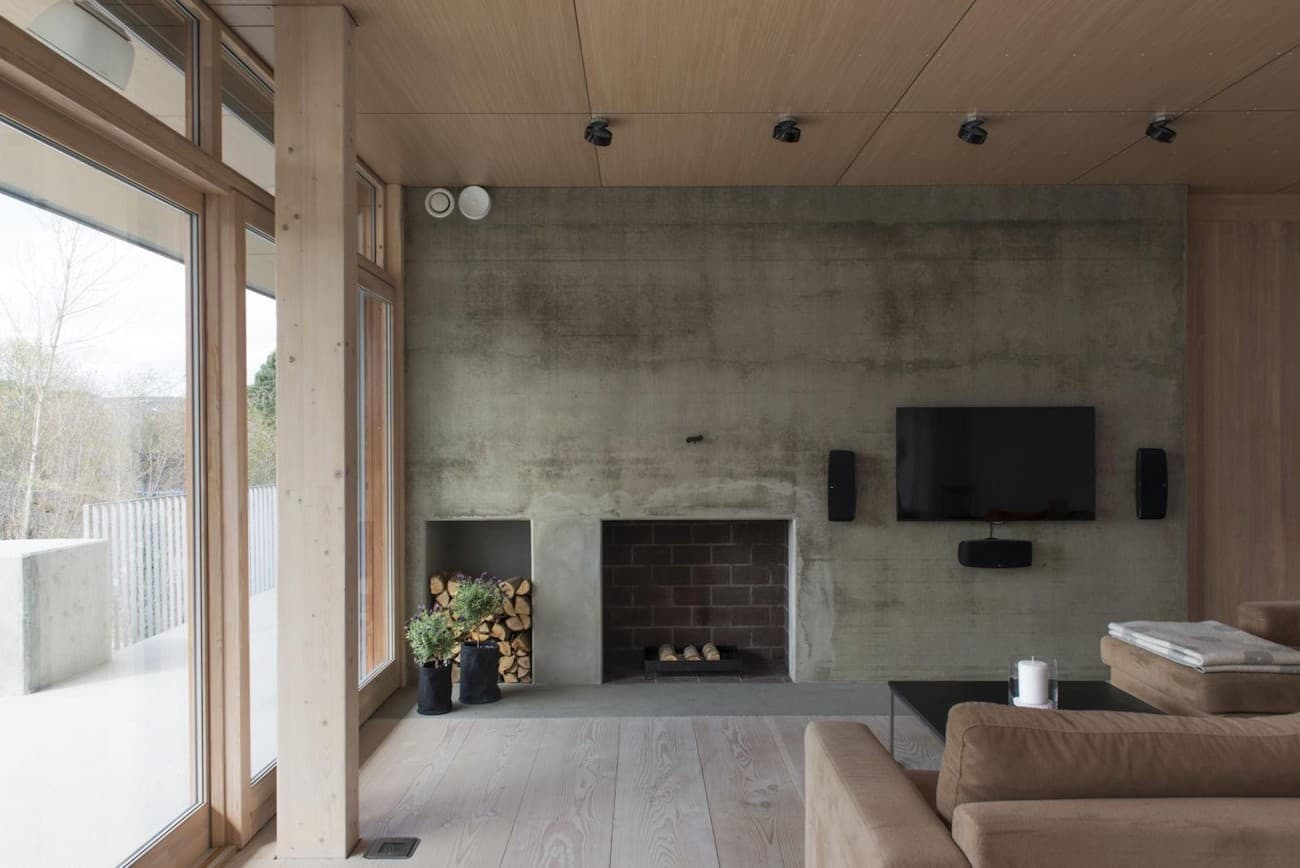 Achieve a rugged and rustic living room style by having a bare gray wall as boasted in this modern design. Carve out a small space for firelight to keep you and your family warm in teeth-grinding winters. To give a fresh feel to this kind of living room, the addition of a few small plants is all you need.