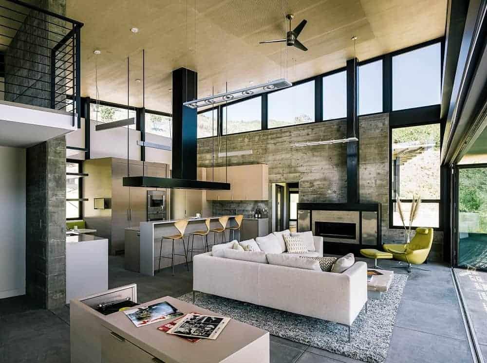 A contemporary home with an open concept style showcasing concrete tiled flooring, wood-paneled ceiling and glazed walls that bring plenty of natural light in. It houses a comfy living space by the fireplace and a kitchen on the side equipped with modern appliances.