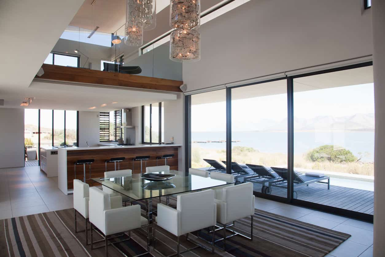 This beach house is the perfect getaway for the whole family to relax and unwind. A square glass table sits delicately in the center with similar shaped white leather seats. Except for the fairy-like cylindrical light fixture, the place is void of any decorations but still manages to shine brightly. Wall-length windows illuminate the whole place and give an unhindered view of the natural beauty outside. The striped coffee colored throw rug in the center brings warmth in the otherwise plain white room.
