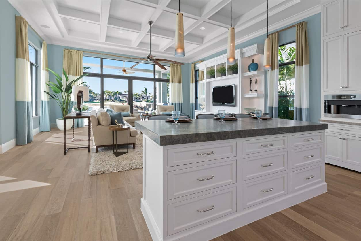The untainted white and genial hues of blue and fawn combine elegantly in this graceful living space. A coffered ceiling and matt wooden floorboards along with a granite kitchen island top and an array of fine decorative pieces together make this open room a modern space with character.