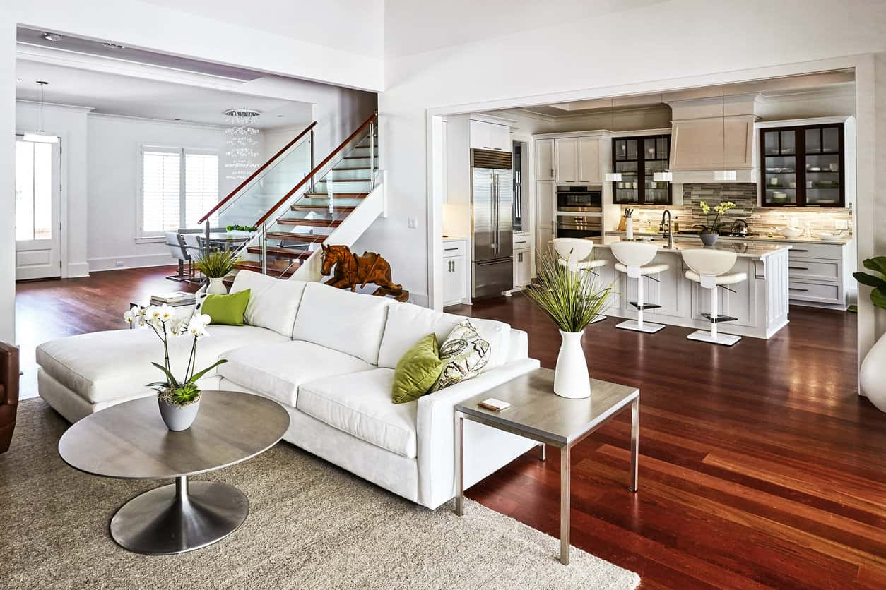 This duplex apartment is a graceful mix of pure white furnishings on a two-toned wooden floor. Modern café-style, counter height stools, and the kitchen island serve as a dining area. Subtle touches of light green accentuate the room while sleek wood-top tables with steel bases give the living area a completely chic look.