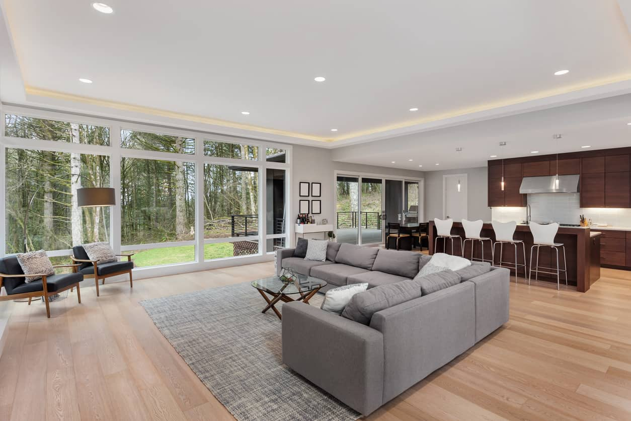 Situated in the middle of a forest clearing, this open room layout has an ample amount of space. The kitchen is kept simple with rich mahogany wooden furnishings that perfectly counterbalance the hushed gray in the living room. Although the glass wall illuminates the place well, ceiling lights are added for more glitz and glory.