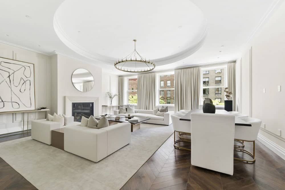 A classy white room with shared living and dining spaces features wainscoted walls, parquet flooring, and a round tray ceiling mounted with a contemporary chandelier. The room is furnished with a modern dining set and a comfy sofa set that sits on a velvet rug.