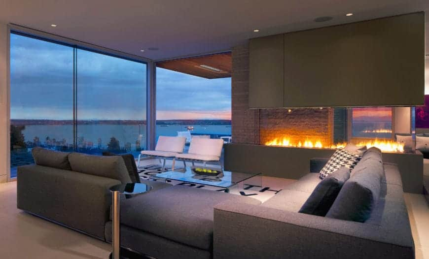 Majestic gas fireplace framed in glass adds warmth and relaxing vibes to this contemporary living room. It also features a V-shaped sectional sofa surrounding a glass center table and a pair of white chairs. Full height glass walls allow a sight on a spectacular beach view.