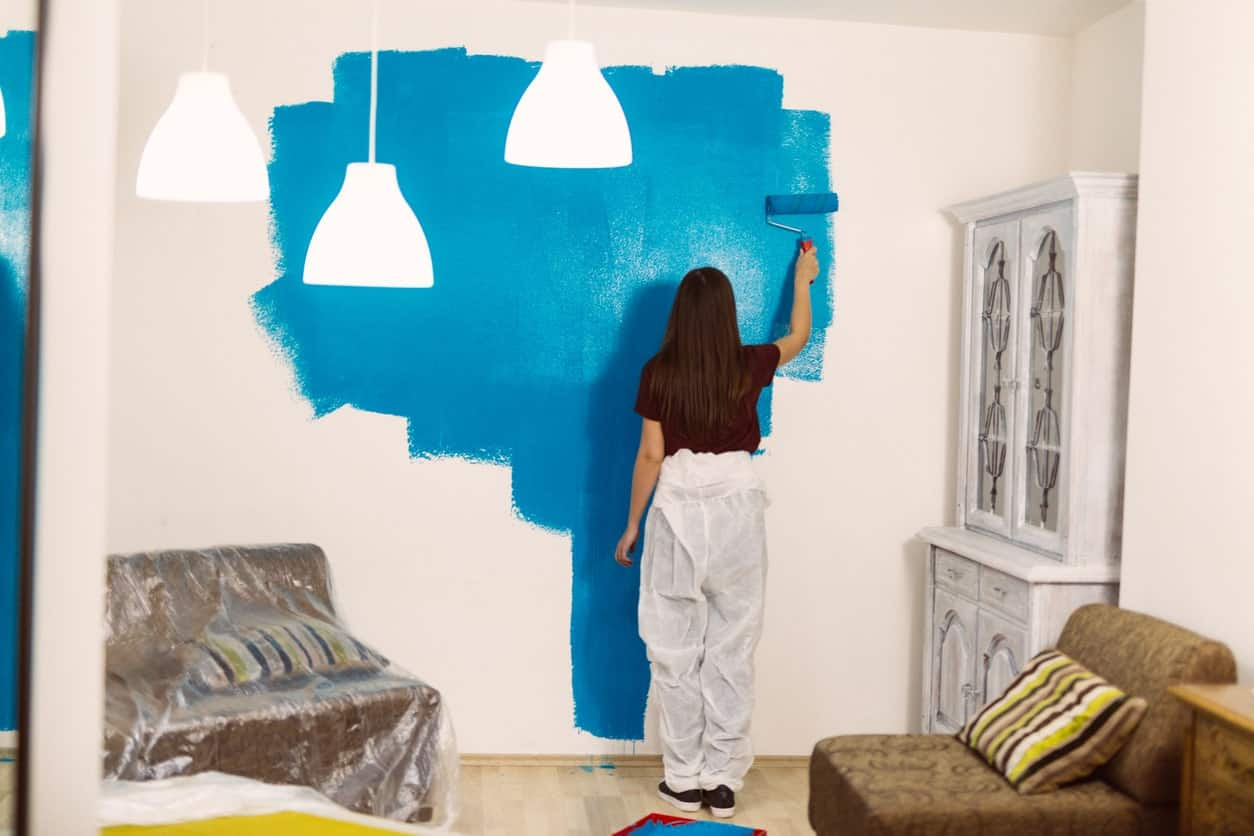 Back profile of a woman painting the interior wall blue.