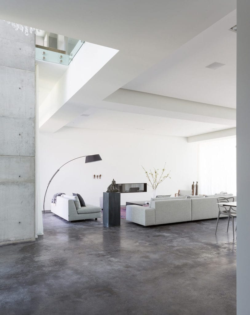 A white smooth wall contrasting the bare concrete floor creates a harmonious living space. It features a gray sectional sofa set and a big arc floor lamp.