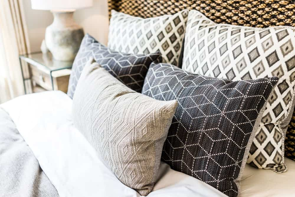 Decorative pillows on bed with comforter.
