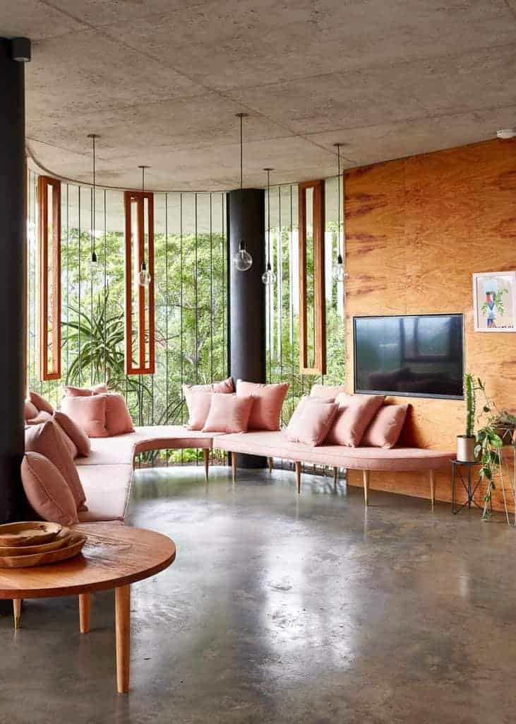 Curved living room highlighted by a salmon pink U-shaped sectional sofa paired with a round wooden side table over a bare concrete floor. Industrial clear glass globe pendant light hanging over a distressed white ceiling complements the glass wall.