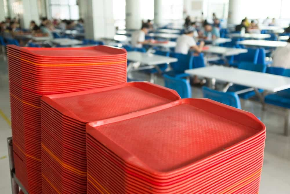 Stacks of red plastic serving trays in a cafeteria.
