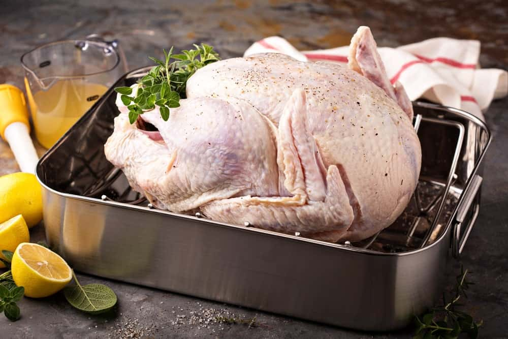 Turkey in a roasting pan surrounded by lemons.