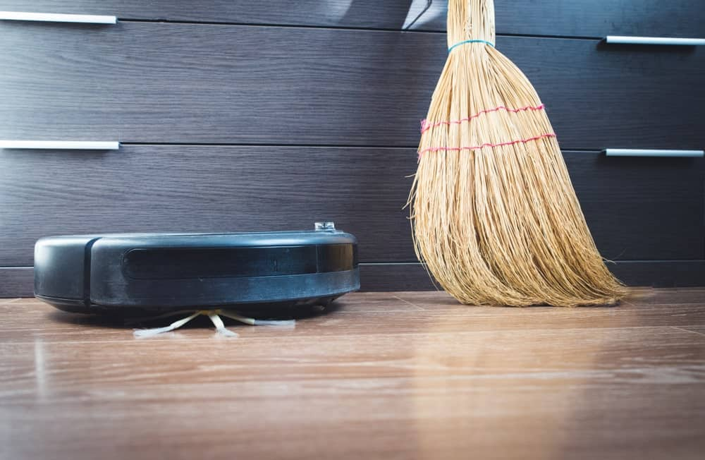 Robot vacuum cleaner beside a broom on hardwood flooring.