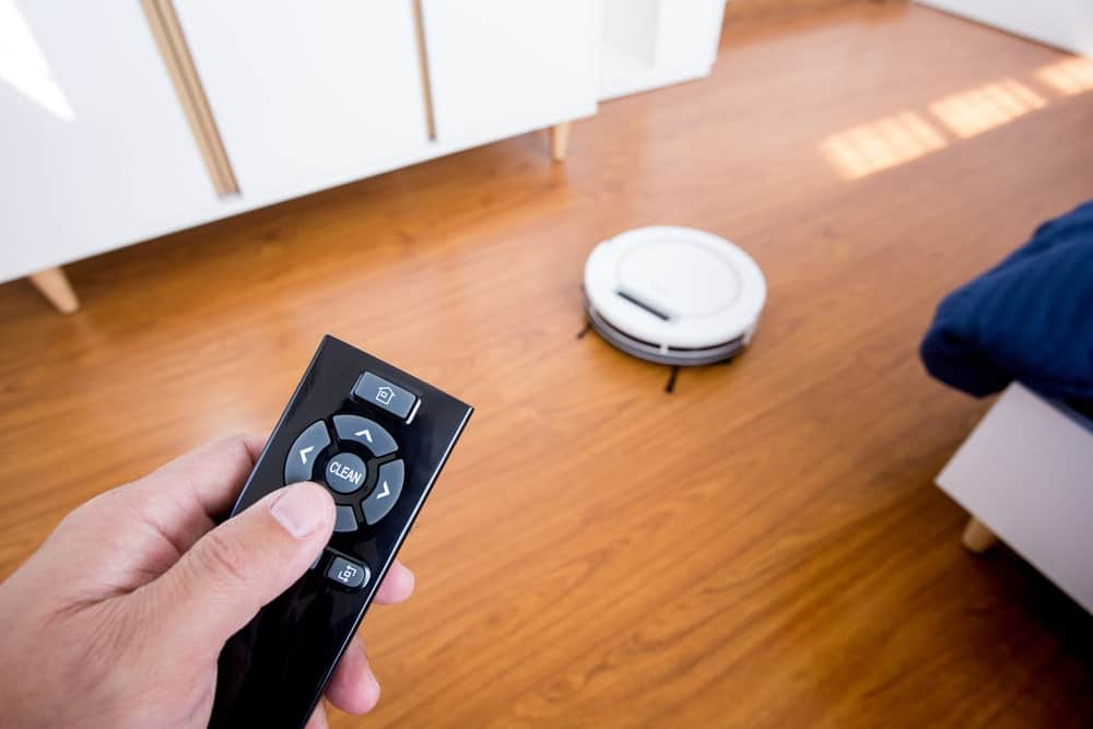 Hand holding a remote control with a robot vacuum on the hardwood flooring as background.