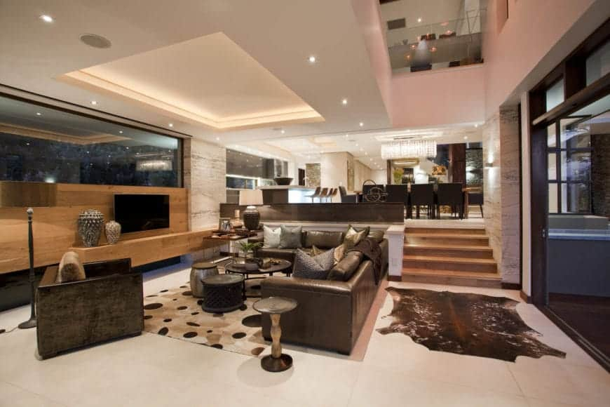 A glamorous living room features a cove ceiling with recessed lighting, dark brown leather furniture, a wooden wall where a flat panel display is mounted and wooden stairs leading to the kitchen.