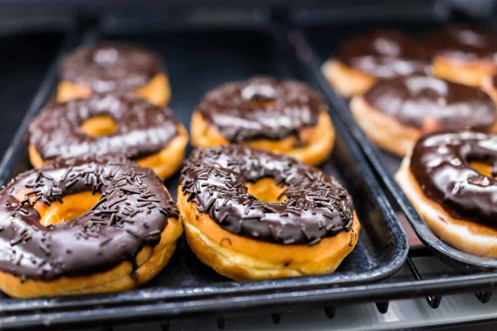 Sprinkled and glazed donuts sitting on a tray