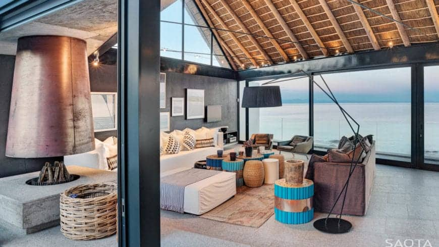 An eclectic living room with tons of varied seating options, an L-shaped white sofa, black arc floor lamp, black wall with gallery frames and glass walls allowing a breathtaking sight to the beach. It is covered by a vaulted ceiling with exposed wooden beams.