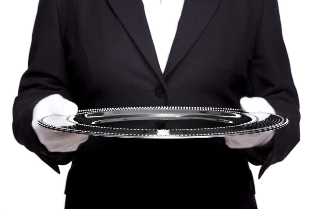 Butler holding an empty silver platter.