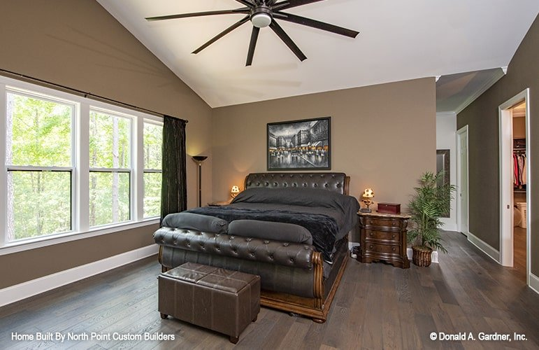 This primary bedroom is nicely complemented with a touch of nature with its fresh potted plants, brown walls, hardwood flooring, and a leather tufted bed adorned with a framed artwork.