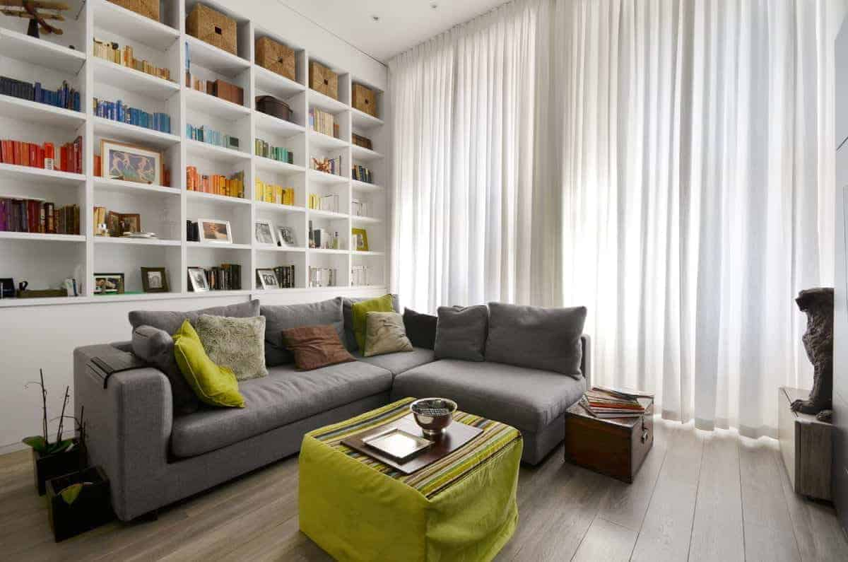 Green and gray look good together on this fresh living room. It has tall glass windows covered with sheer curtains, white built-in shelves and an L-shaped gray sofa paired with coffee table with green cover and a wooden side chest over a hardwood flooring.