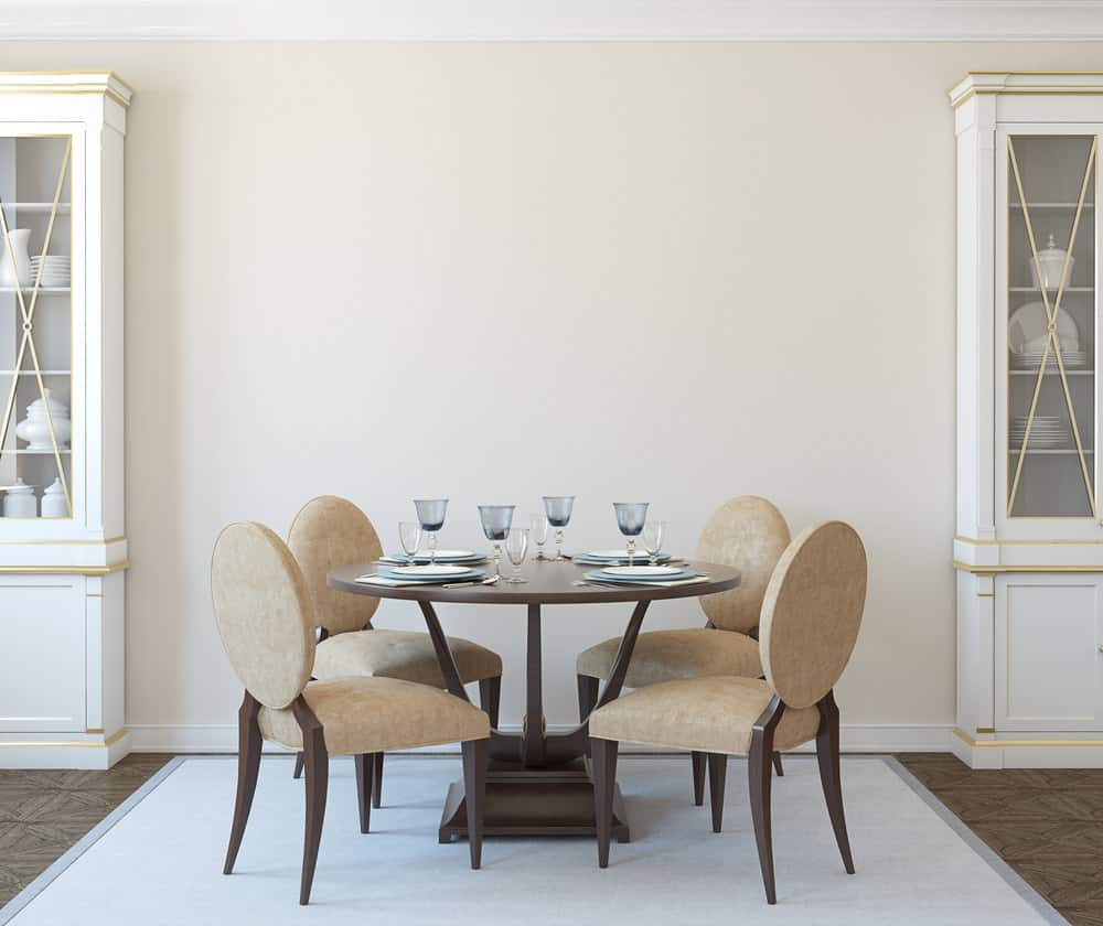 This dining room features Louise-style chairs, popular during the Renaissance. However, it has a very modern style with minimal decorations. The dark round dinner table showcases the beautiful glass and china tableware to the maximum. The warm tones of the furniture are offset by the cool blue of the carpet beneath the table.