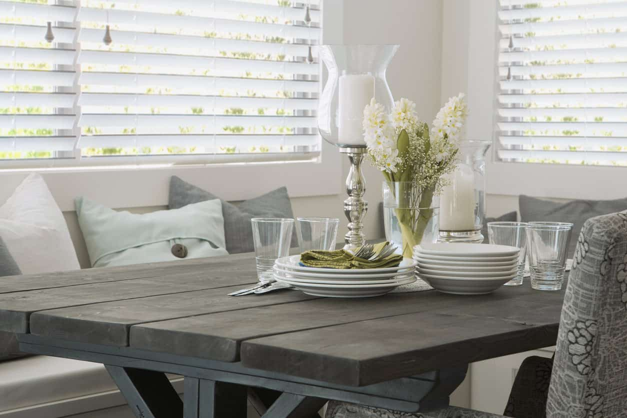 This beautiful dining area is filled with rustic charm. The table is made of plain gray wood and is set with centerpieces of white floral sprigs and a white taper. The table is surrounded by armchairs and banquettes with pastel colored pillows and is fitted into the corner of the room, making a cozy nook.