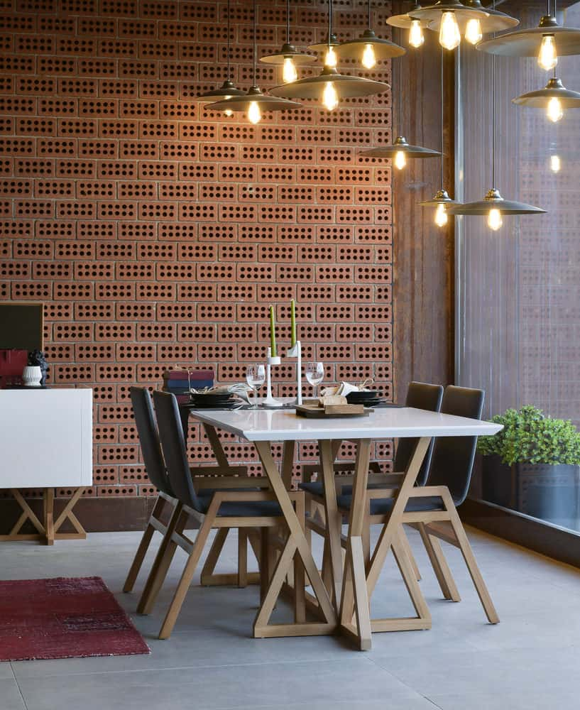 What's so great about this dining room style is the number of overhead lamps that exude a warm golden glow. The furniture is follows modern design aesthetics and is easy to clean and maintain. But the most striking feature of the dining area is the red brick wall, filled with hundreds of cubbyholes.