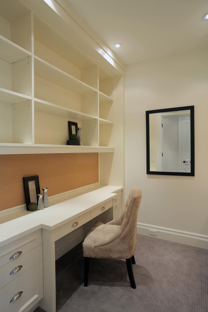 Small home office with recessed lighting, built-in shelving, built-in desk with drawers and paired with an accent velvet chair, a wall mirror, and carpet flooring.